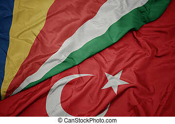 waving colorful flag of turkey and national flag of seychelles.