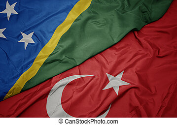 waving colorful flag of turkey and national flag of Solomon Islands.
