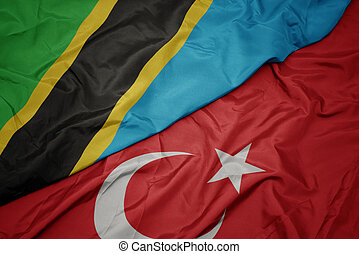 waving colorful flag of turkey and national flag of tanzania.