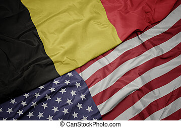 waving colorful flag of united states of america and national flag of belgium. macro