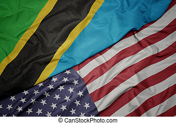 waving colorful flag of united states of america and national flag of tanzania. macro