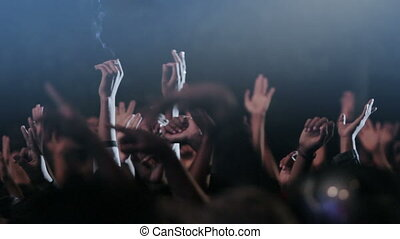 Waving crowds at concert - hands of crowds reaching up in...