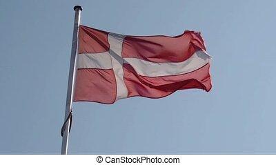 Waving Danish flag on a blue sky, retro film toned