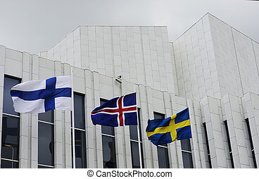 waving Finnish, Swedish, Icelandic flags against of Finlandia Hall