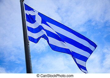 Waving flag of Greece on flagpole. Blue sky with few clouds background.