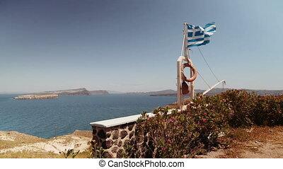 Waving flag of Greece on the coast Santorini