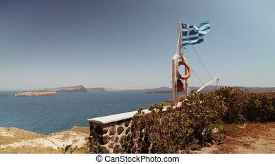Waving flag of Greece on the coast Santorini