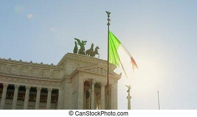 Waving flag of Italy and historic Vittorio Emanuele II...