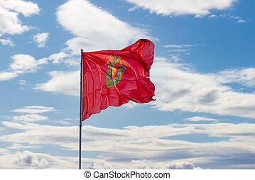 Waving Flag of Krasnoyarsk Krai on a pole against cloudy sky background
