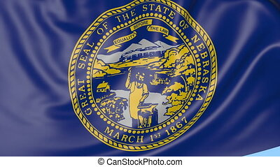 Waving flag of Nebraska state against blue sky.