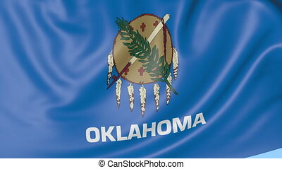 Waving flag of Oklahoma state against blue sky.