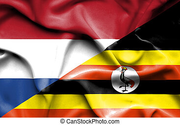 Waving flag of Uganda and Netherlands