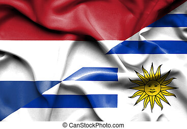 Waving flag of Uruguay and Netherlands