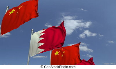 Waving flags of Bahrain and China on sky background,...