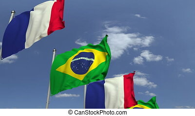 Waving flags of Brazil and France on sky background,...