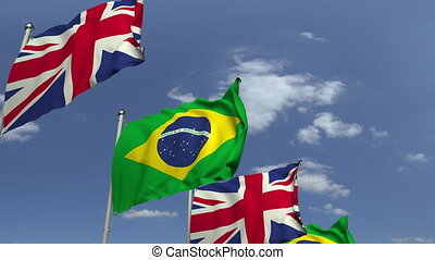 Waving flags of Brazil and the United Kingdom on sky...