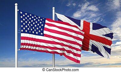 Waving flags of USA and UK on flagpole, on blue sky...