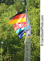Waving flags on the flagpole of different countries