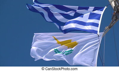 Waving Greek and Cyprian flags agaist the blue sky in strong...