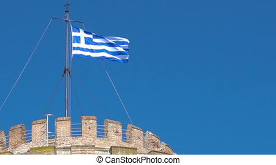 White Tower in Thessaloniki - Waving greek flag on the top...