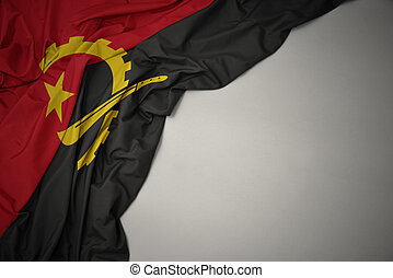 waving national flag of angola on a gray background.