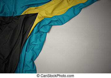 waving national flag of bahamas on a gray background.