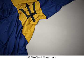 waving national flag of barbados on a gray background.
