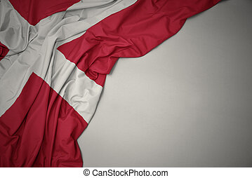 waving national flag of denmark on a gray background.