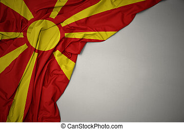 waving colorful national flag of macedonia on a gray background.