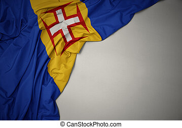 waving national flag of madeira on a gray background.