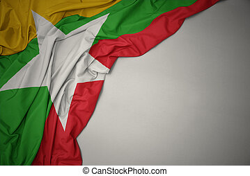 waving national flag of myanmar on a gray background.