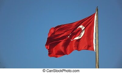 Waving national flag of Turkey on a background blue sky. A...