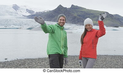 Waving people saying hello with hand on Iceland hike. Cheerful happy hikers couple hiking by glacier and glacial lagoon / lake Fjallsarlon Vatnajokull National Park in Icelandic nature. RED EPIC.
