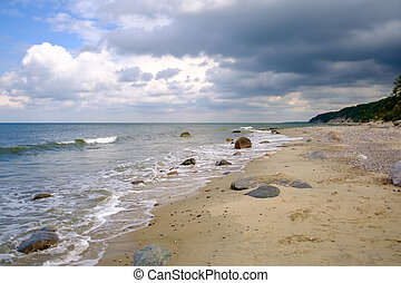 Waving sea and sandy shore on cloudy day