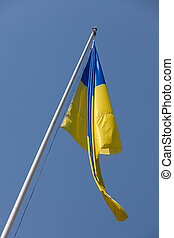 Waving Ukrainian Flag and flagstaff on the blue sky background