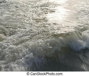 Waving water. Sailing ship has left behind the waves.