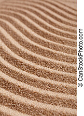 Wavy pattern on a beach in the summer. The textured surface of sand on the beach after a strong wind in the form of waves close up.