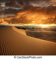 Wavy sand dune at sunset on background dramatic sky clouds