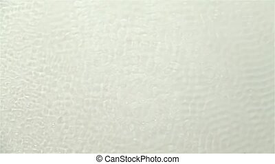 Wavy surface of water caused by sound vibrations. White...