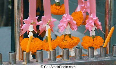 Wax candles and flowers near traditional Buddhist altar in...