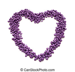 Wax for depilation of purple color in the shape of a heart. On white background. Close-up.