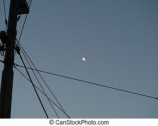 Waxing gibbous moon over blue sky background behind wires