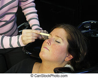 waxing her eyebrows - A woman gets her eyebrows waxed.