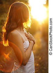 Young girl holding her hands on her heart looking towards the setting sun