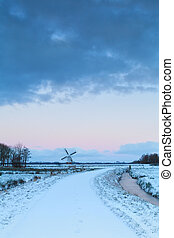 way to windmill on snow at sunrise