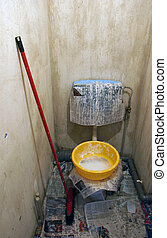 Toilet in austere state prepared for painting and tiling