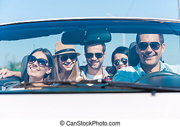 We always travel together! Group of young happy people enjoying road trip in their white convertible
