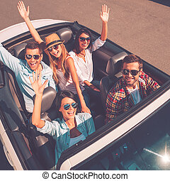 We always travel together! Top view of young happy people enjoying road trip in their white convertible and raising their arms