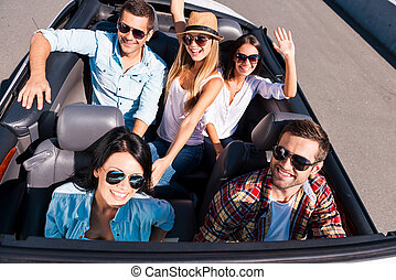 We always travel together. Top view of young happy people enjoying road trip in their white convertible and raising their arms