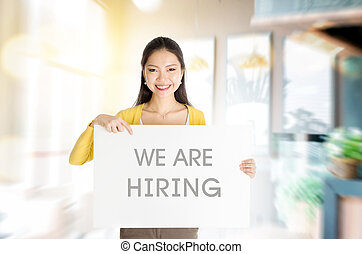 """We are hiring - Young Asian woman hand holding """"we are..."""